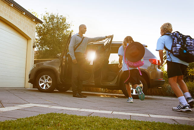 Father opening door of family car for his children